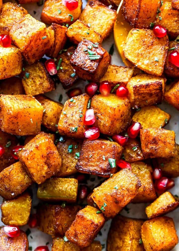 up close photo of Cinnamon Roasted Butternut Squash Recipe with pomegranates and rosemary