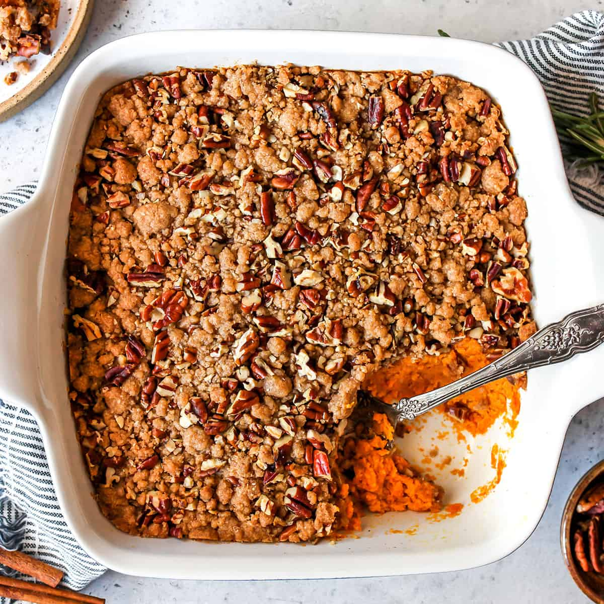 overhead view of sweet potato casserole with pecans in a baking dish
