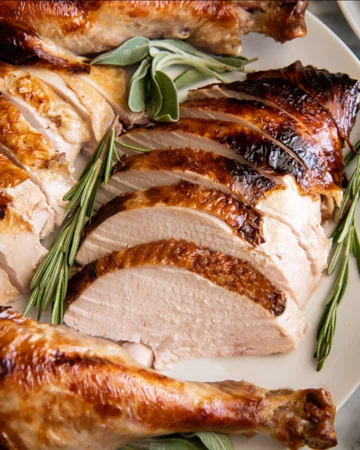 overhead view of roast turkey carved on a plate with herbs around it