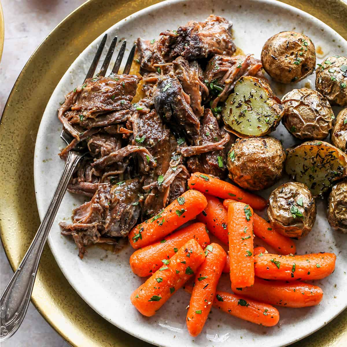 Slow Cooker Pot Roast on a plate with carrots and potatoes