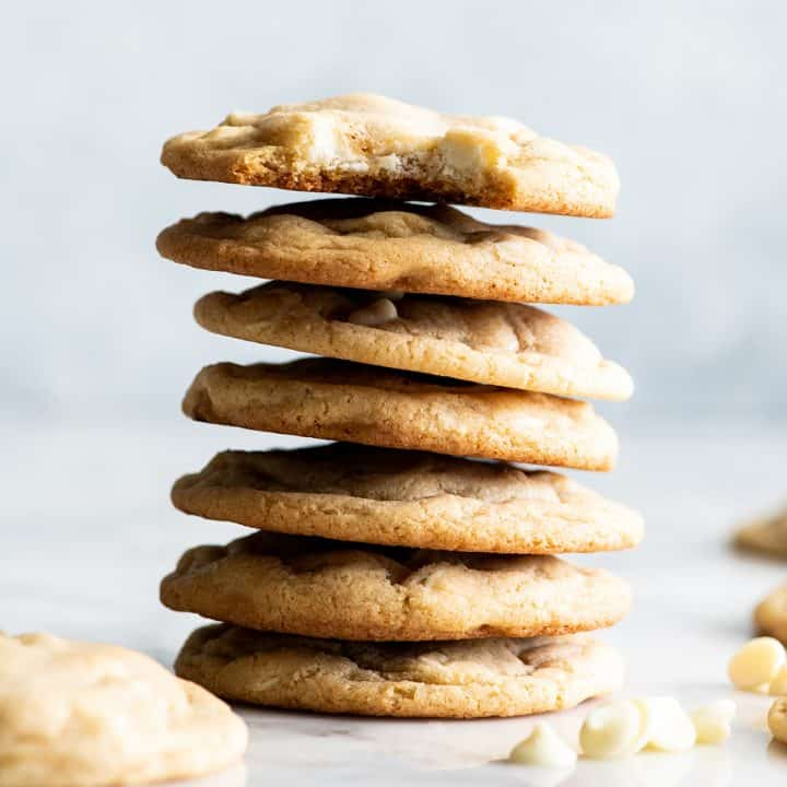 stack of 7 White Chocolate Chip Cookies, the top one has a bite taken out of it
