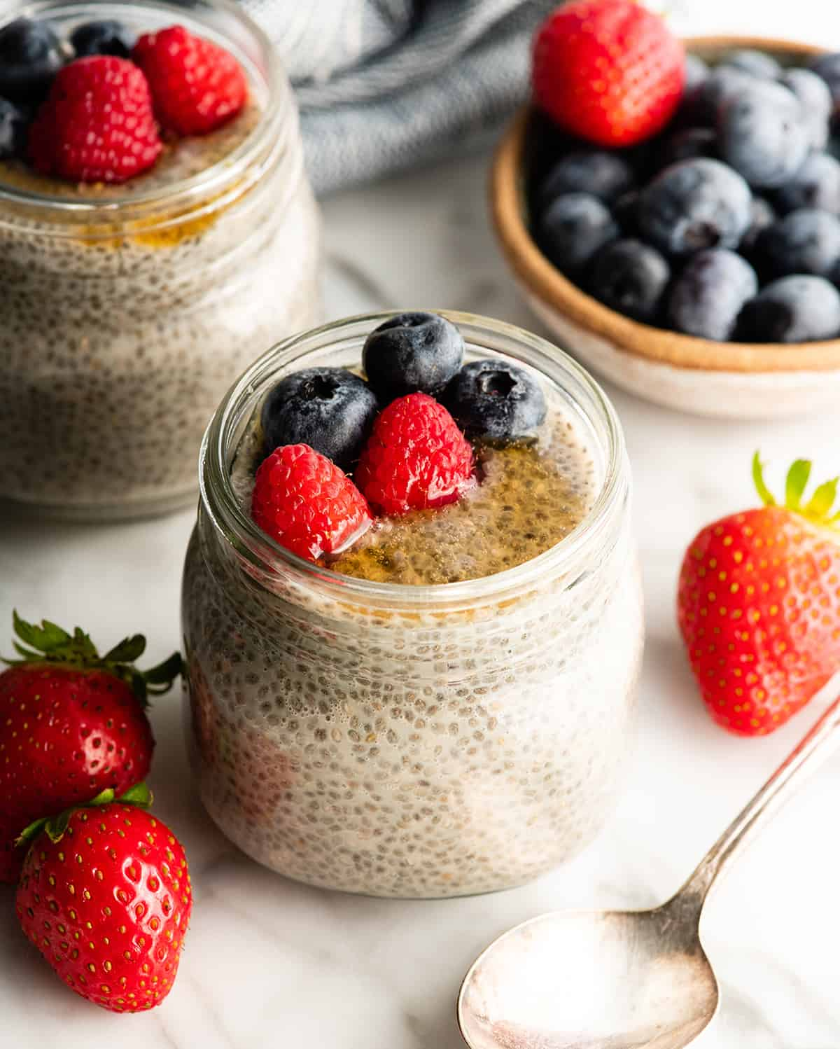 two jars of chia pudding with berries and honey