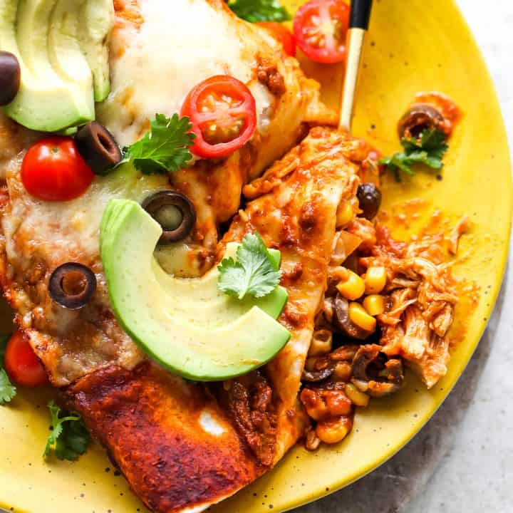 overhead photo of two chicken enchiladas on a plate with a bite showing the inside