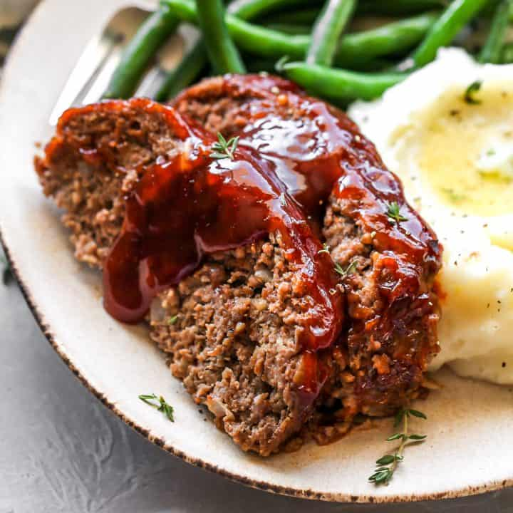 front view of two slices of the Best Meatloaf on a plate with beans and mashed potatoes