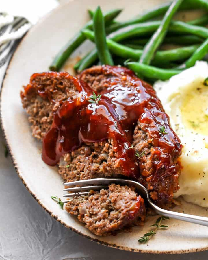 two slices of meatloaf on a plate with a fork taking a bite