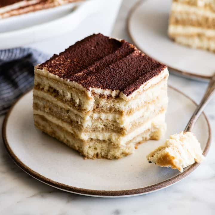 a piece of the Best Tiramisu on a plate with a bite taken out of it