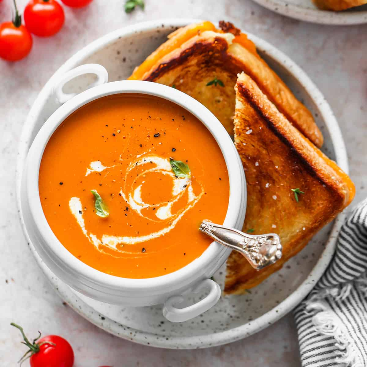 a bowl of Homemade Tomato Soup with grilled cheese on the side