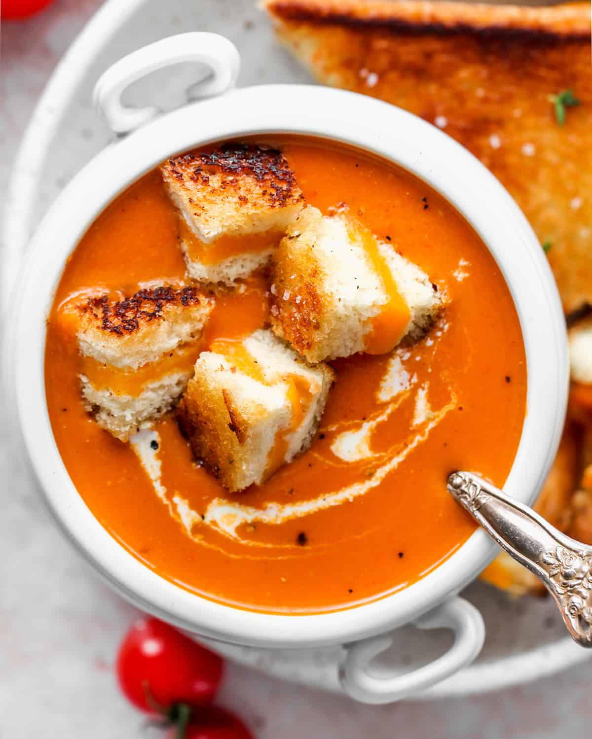 bowl of Homemade Tomato Soup with grilled cheese pieces inside
