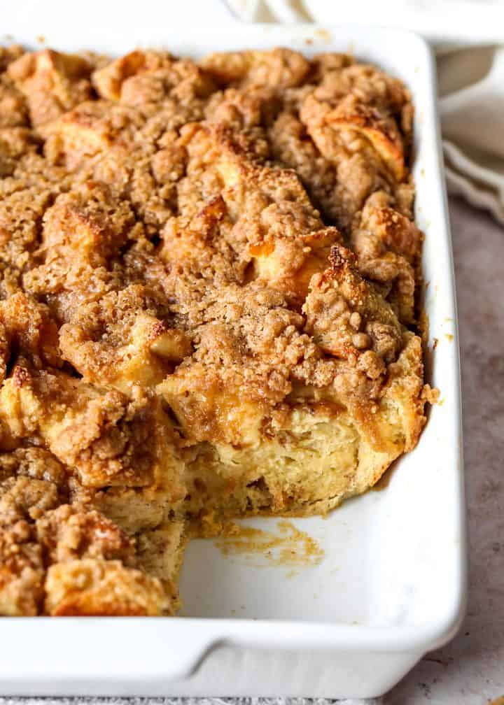 front view of Baked French Toast Casserole in a baking dish with a piece removed