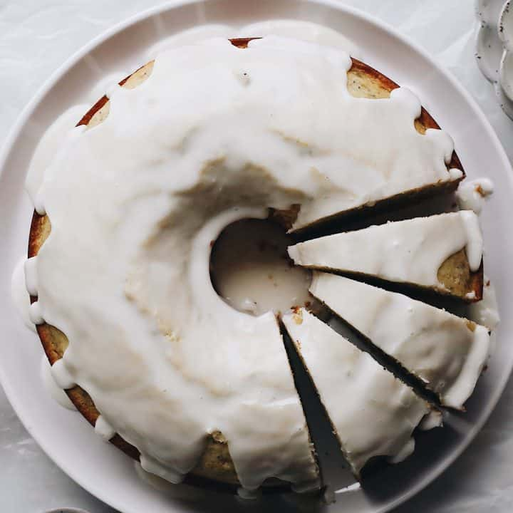 overhead photo of a Poppy Seed Cake on a serving plate with 3 slices cut