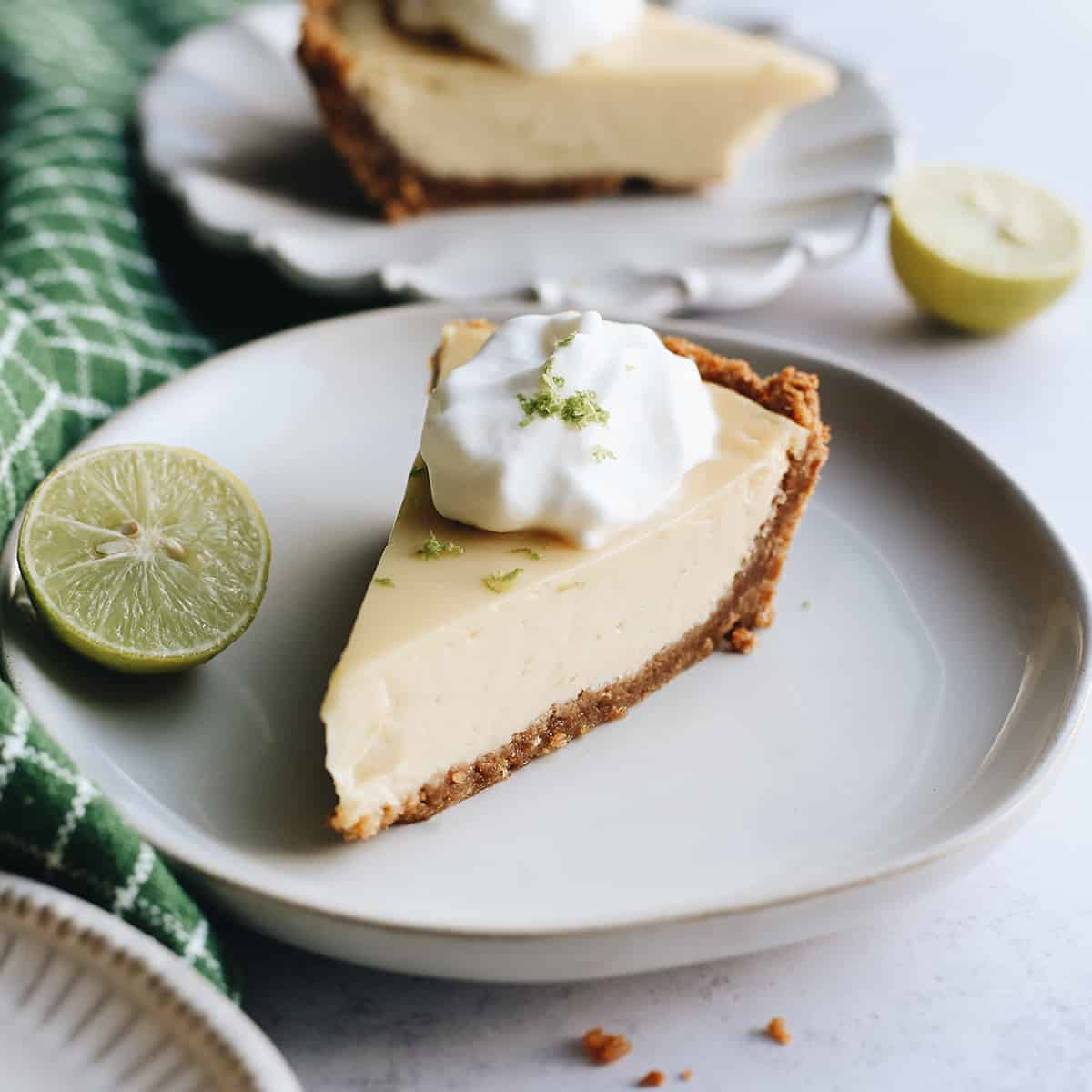 a slice of Key Lime Pie on a plate with whipped cream on top