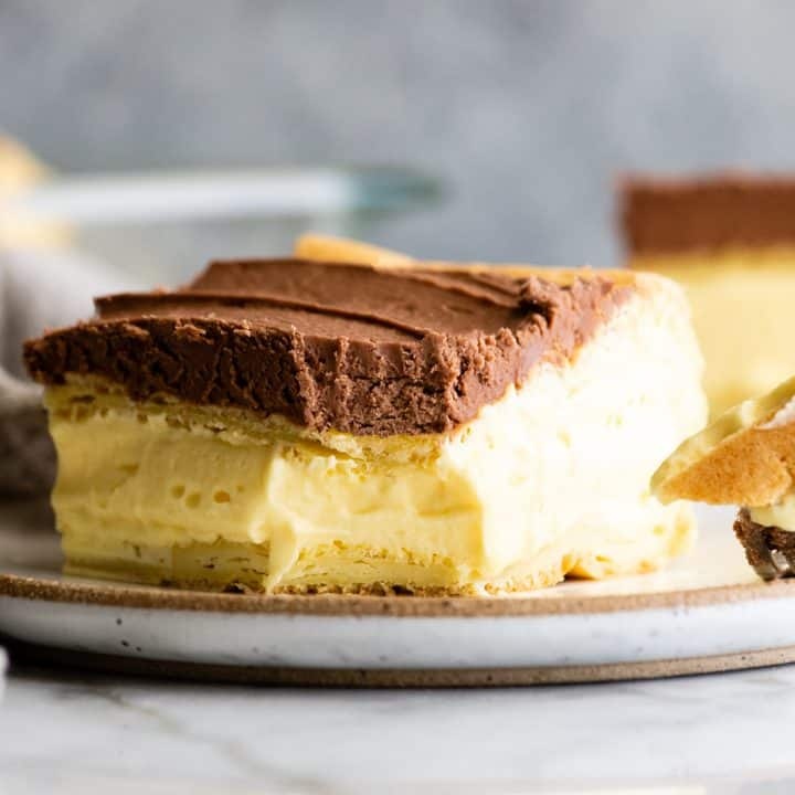 piece of Chocolate Eclair Cake on a plate with a bite taken out of it