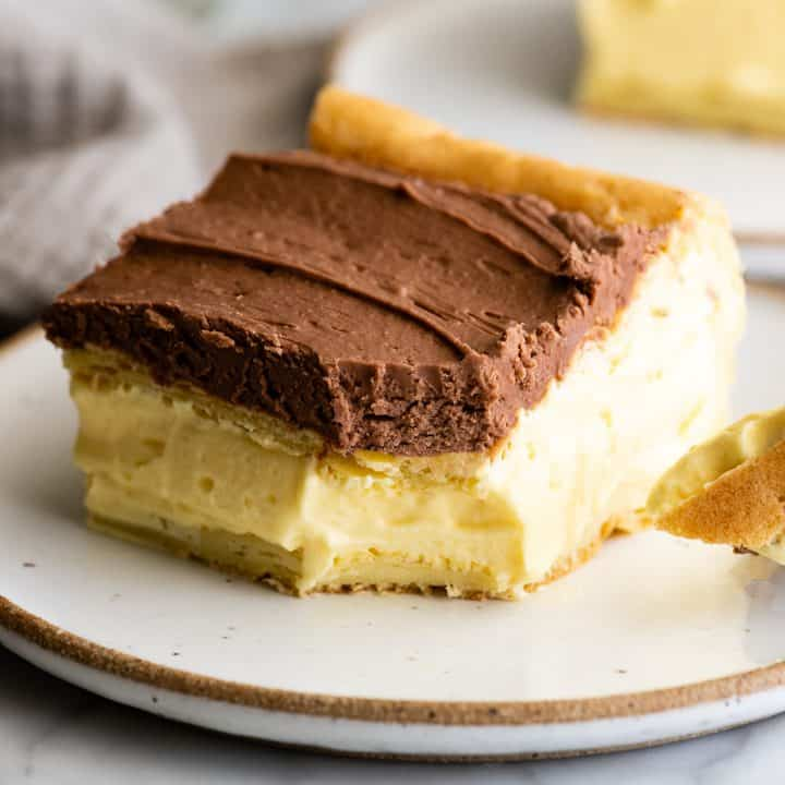 piece of eclair cake on a plate with a bite taken out of it