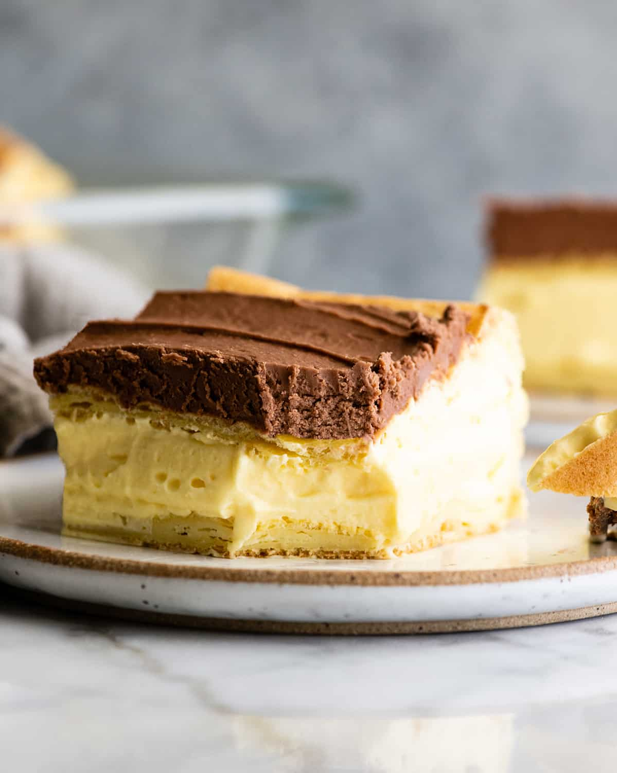 a piece of eclair cake on a plate with a bite taken out of it