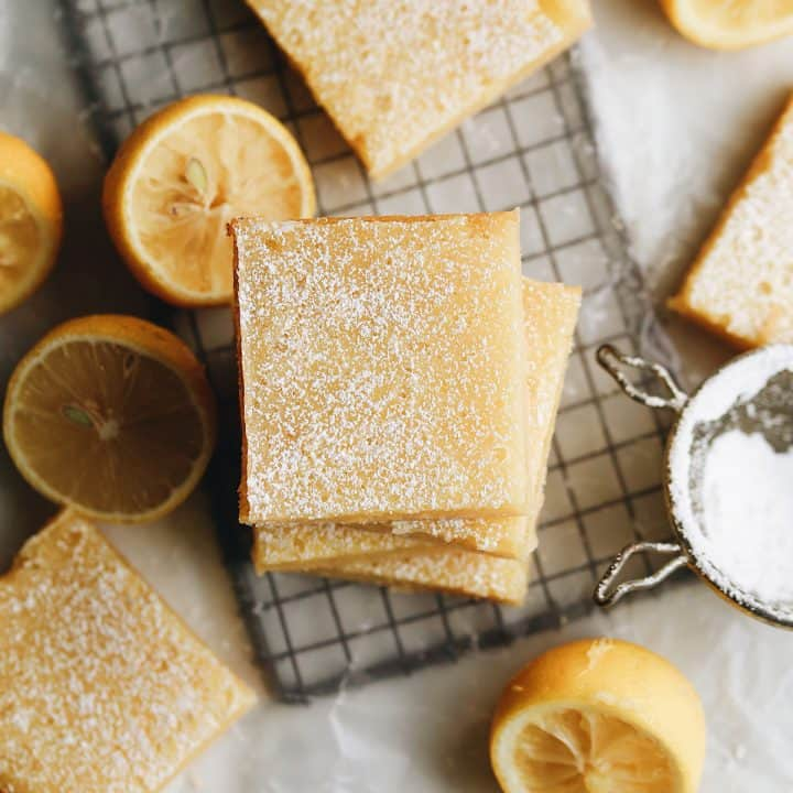 overhead view of a stack of lemon bars with lemons and other bars around it