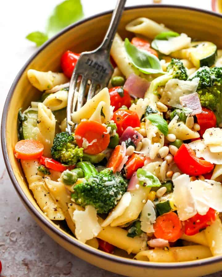 pasta primavera in a bowl with a fork taking a bite