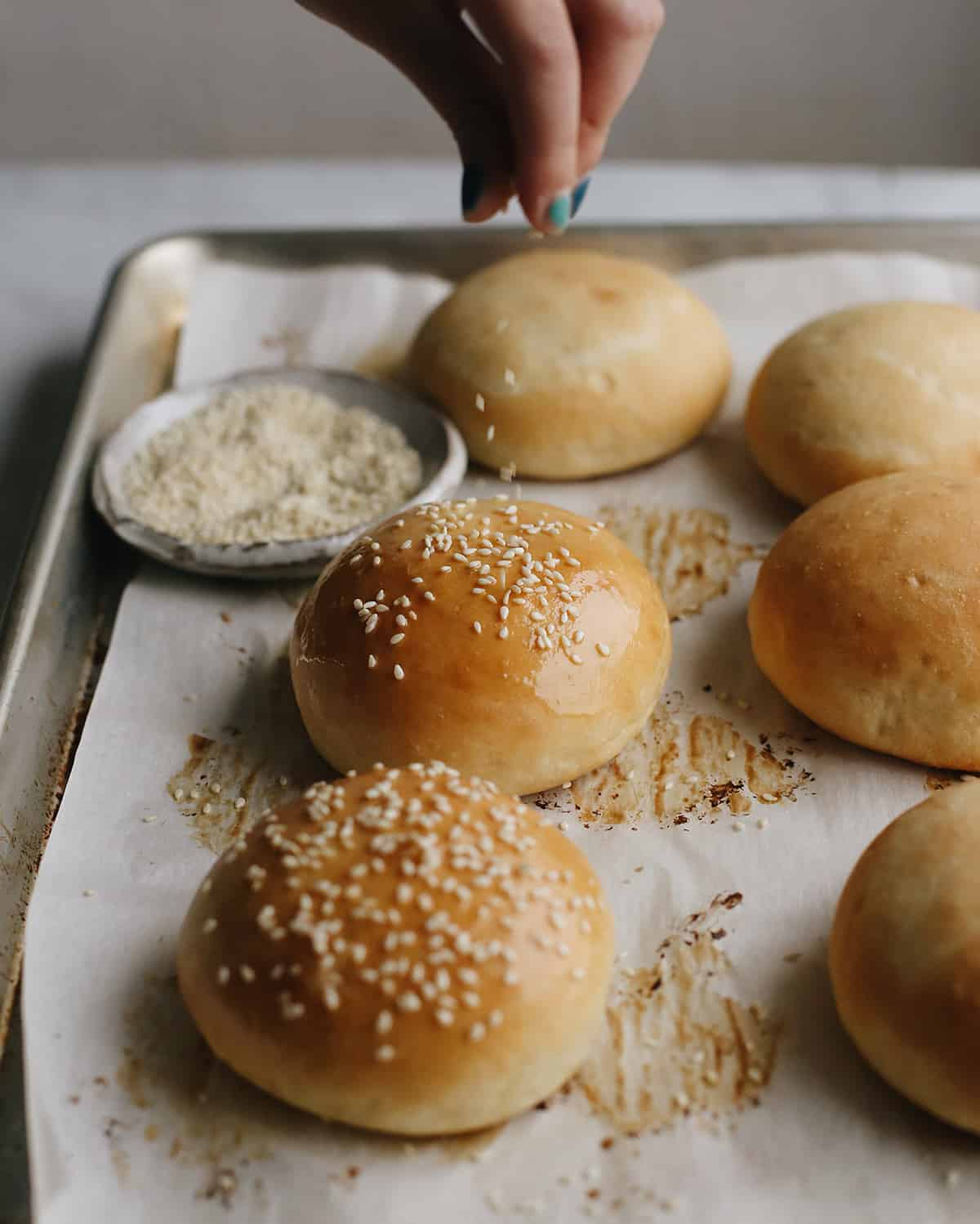 front view of sesame seeds being sprinkled on Homemade Burger Buns