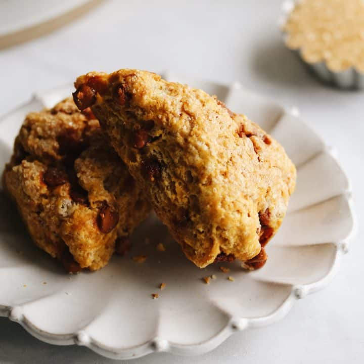 two pumpkin scones on a white plate