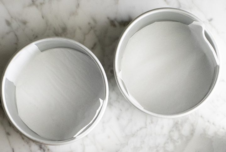 photo of two round cake pans lined with parchment paper