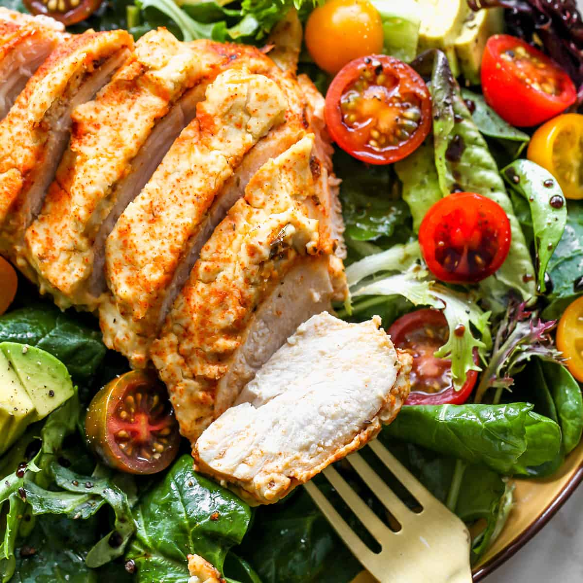 overhead photo of baked hummus chicken sliced over a salad