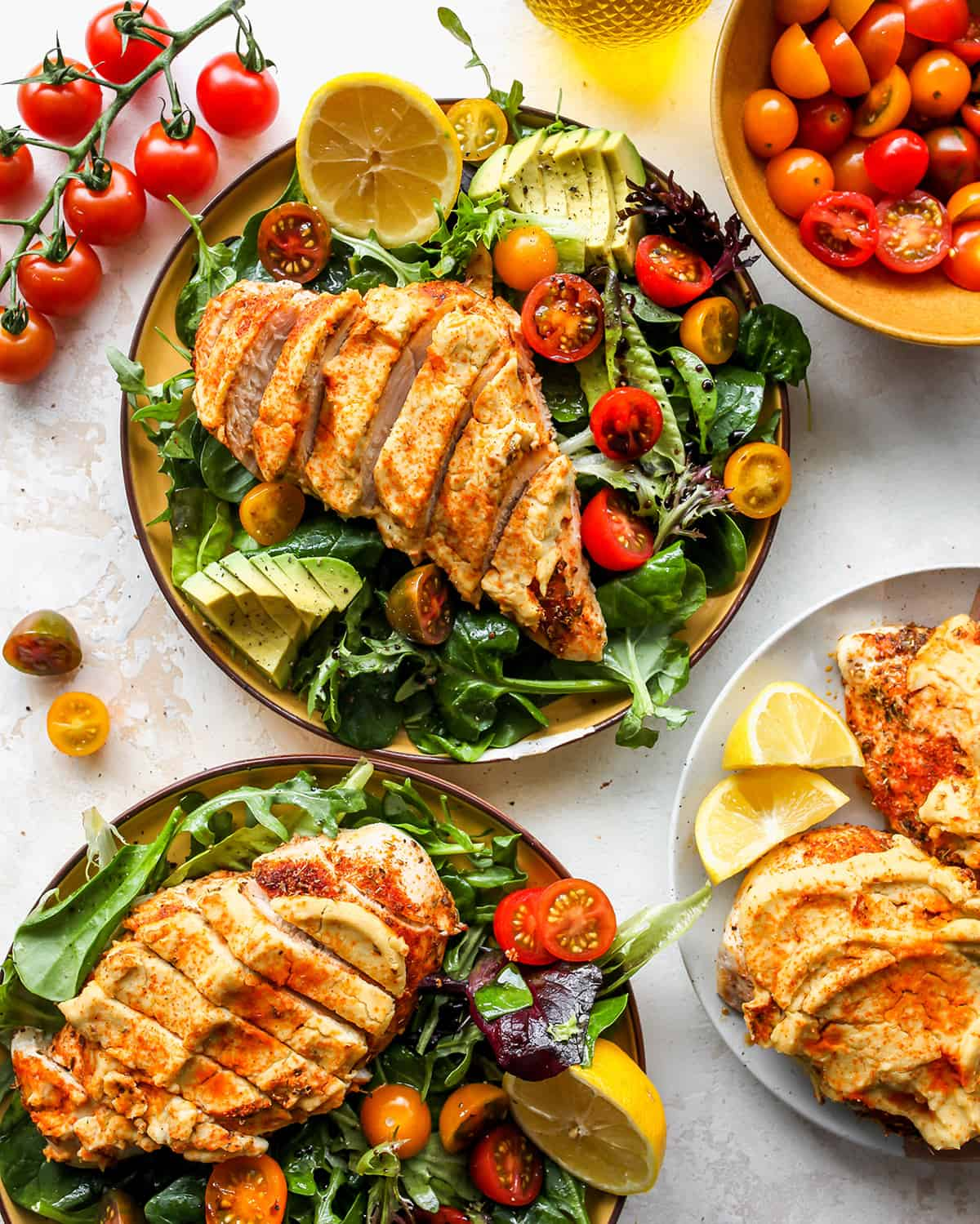 two plates of Baked Hummus Chicken over salad