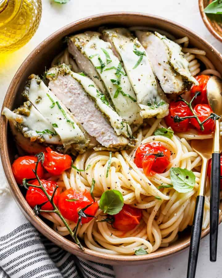 Baked pesto chicken cut into slices over pasta with red tomatoes