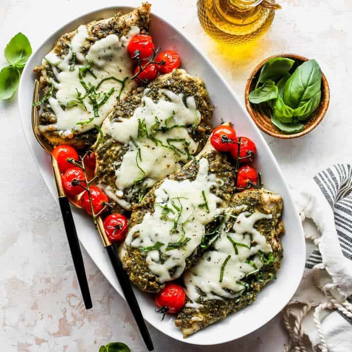 four pesto chicken breasts on a platter with baby tomatoes
