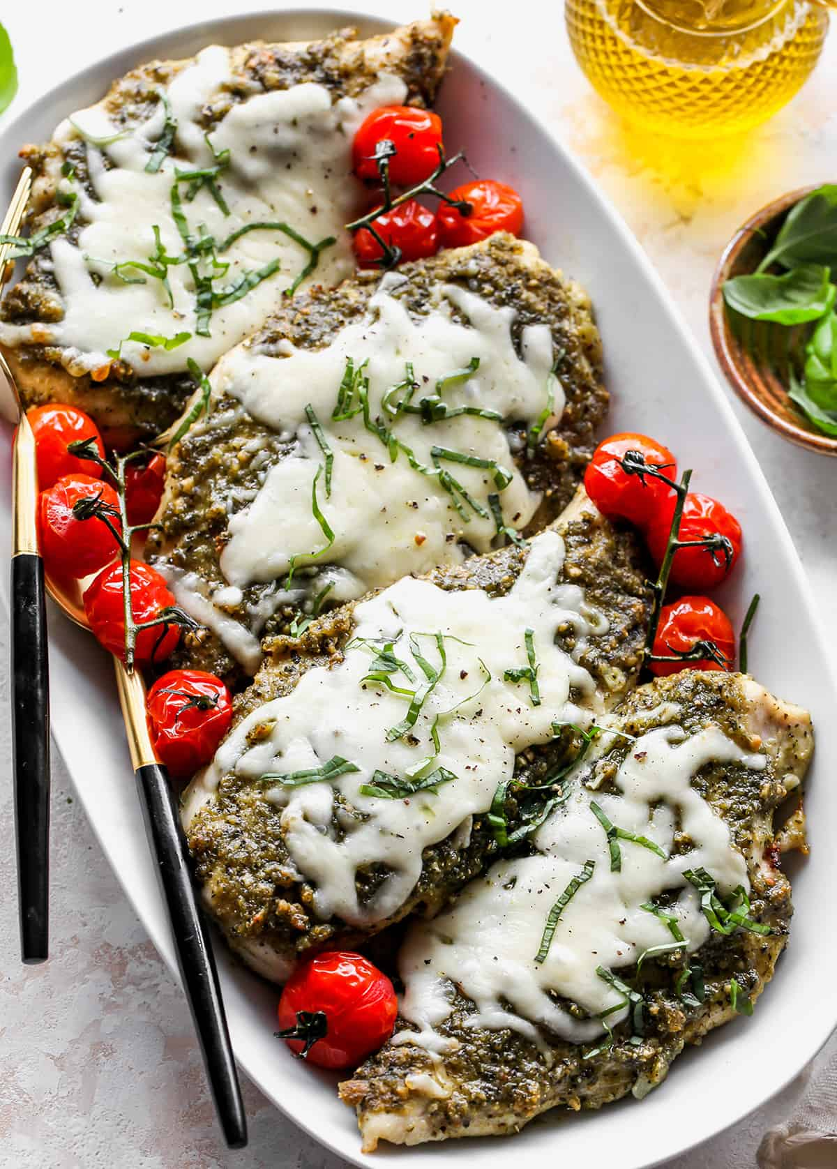 four baked pesto chicken breasts on a platter with tomatoes