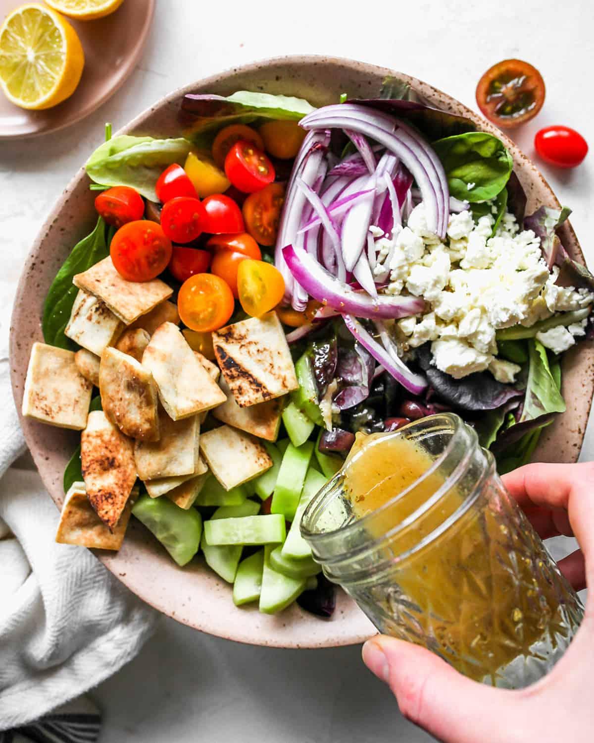 Greek Salad Dressing being poured over a Greek salad