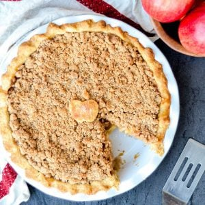 Overview photo of an apple pie with a piece cut out.