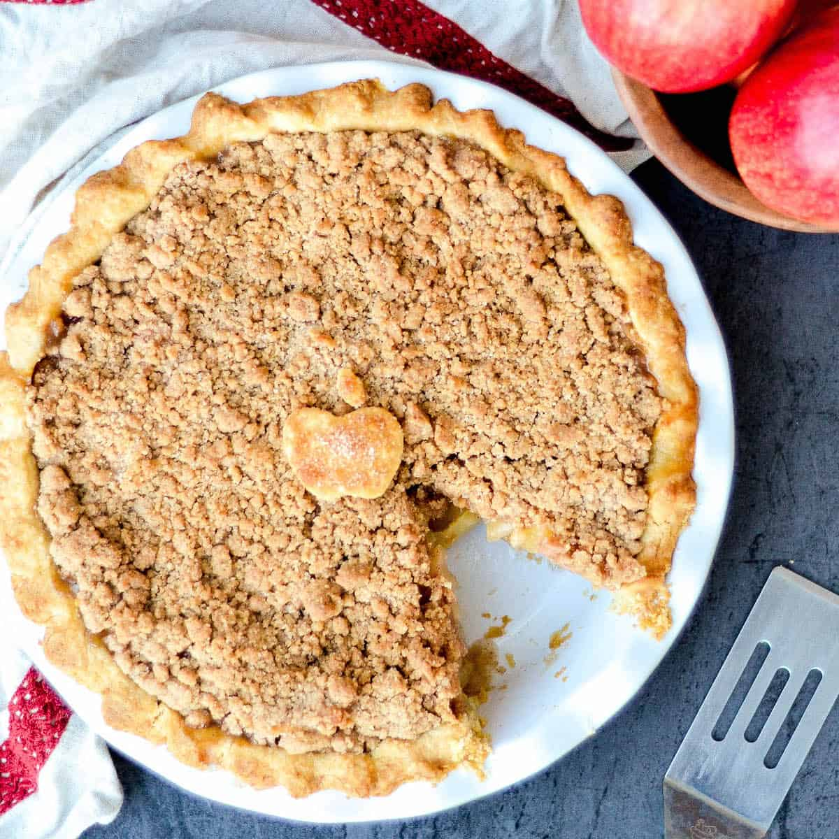 Overhead view of a pie dish with The best homemade Apple Crumble Pie with a piece removed.
