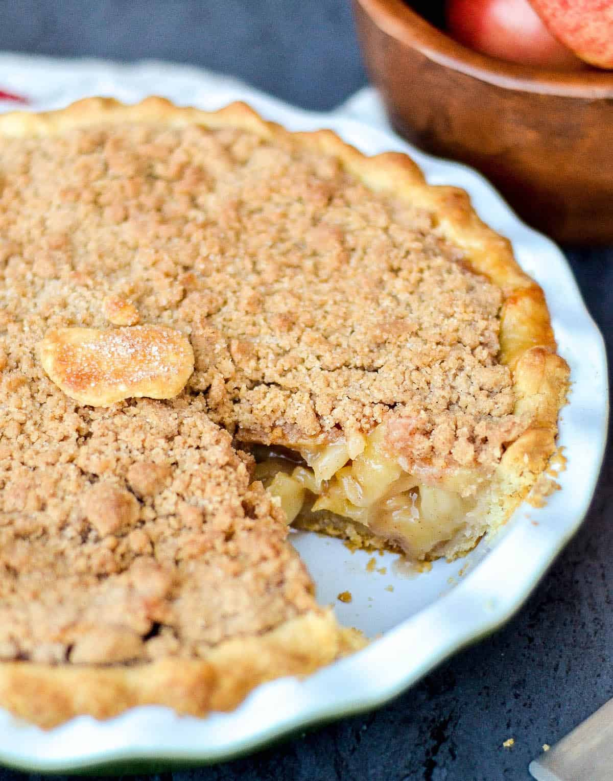Front view of homemade apple crumble pie in a pie dish with a piece removed.
