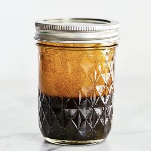 Side view of balsamic vinaigrette in a mason jar with silver lid on it.
