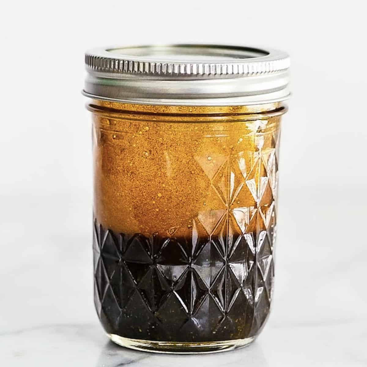 Side view of Balsamic Vinaigrette in mason jar with silver lid on.