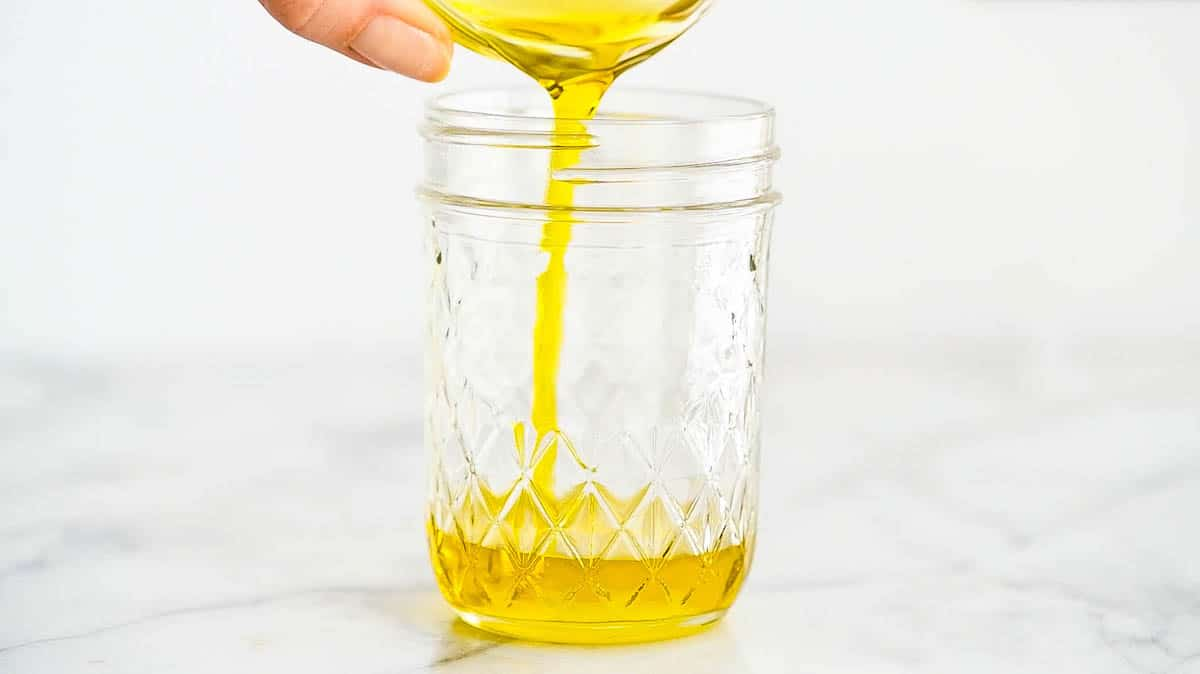 Oil being poured into mason jar.