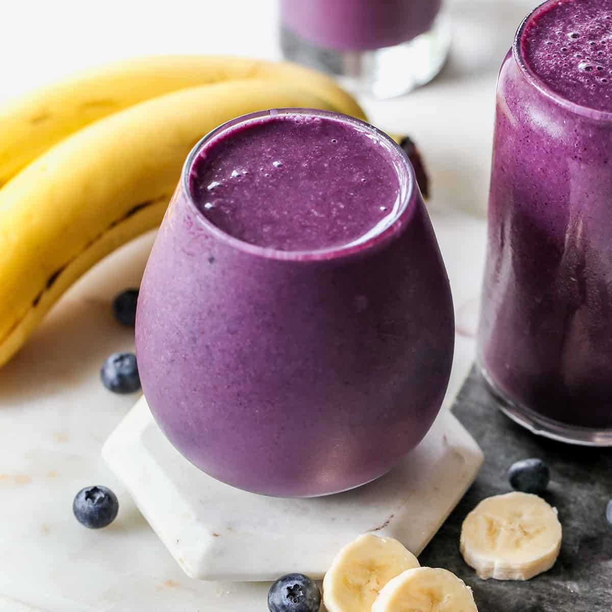 front view of a glass filled with blueberry smoothie with bananas and blueberries around it