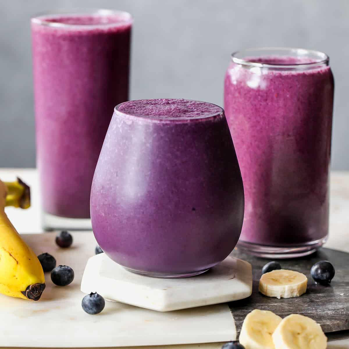 front view of three glasses filled with Blueberry Smoothie with bananas and blueberries around them