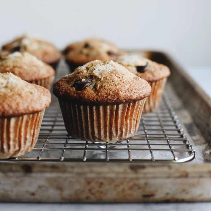 front view of 6 Banana Chocolate Chip Muffins on a wire rack cooling