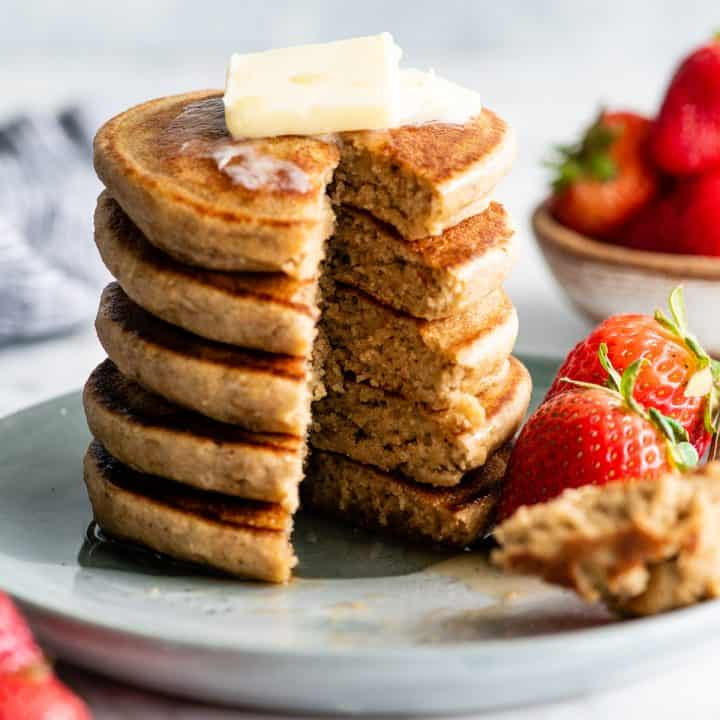 front view of a stack of 5 banana oat pancakes with butter and syrup and a piece cut out of the stack