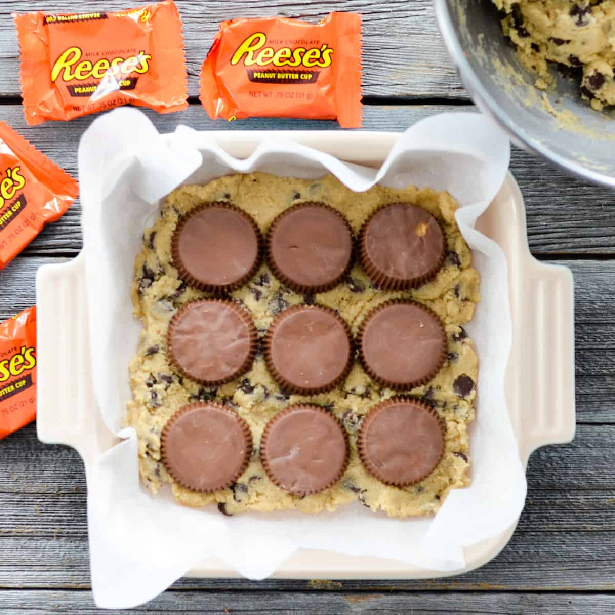 Overhead view of a baking dish with Candy Cookie Bars dough with three rows of three Reese's cups on top.