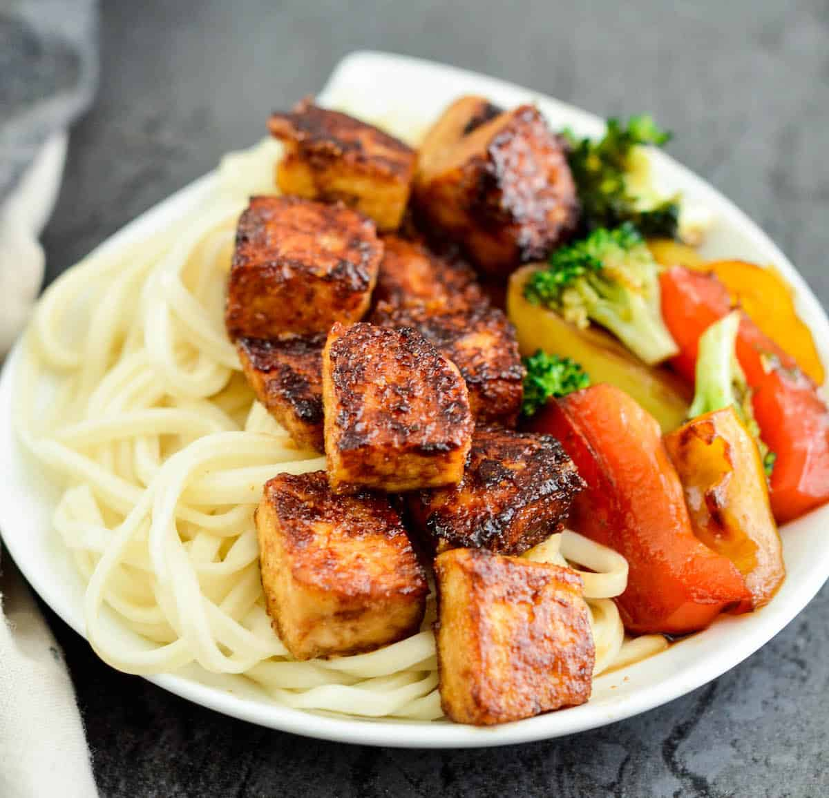 Side view of crispy tofu with hoisin sauce on a plate with noodles and stir fried veggies.