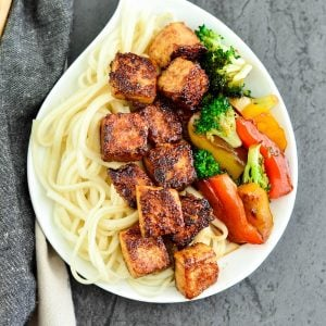 Overhead view of crispy tofu with hoisin sauce on a plate with noodles and stir fried veggies.