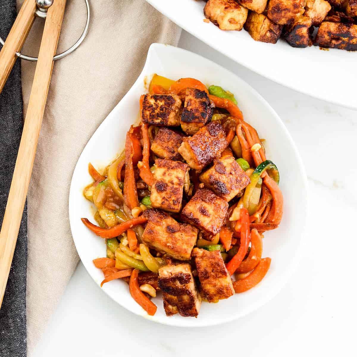 Overhead view of crispy tofu with hoisin sauce recipe on a white plate over stir fried veggies.