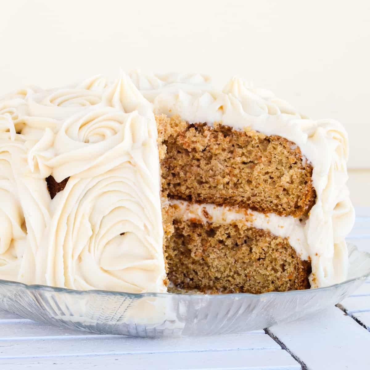 front view of a carrot cake with a slice cut out of it