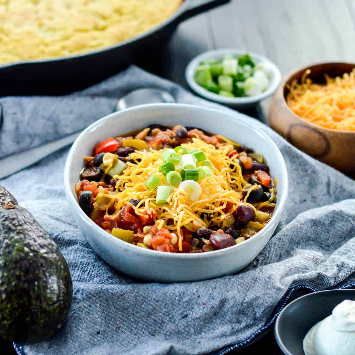 front view of The BEST Healthy Crockpot Chicken Chili in a bowl with toppings.