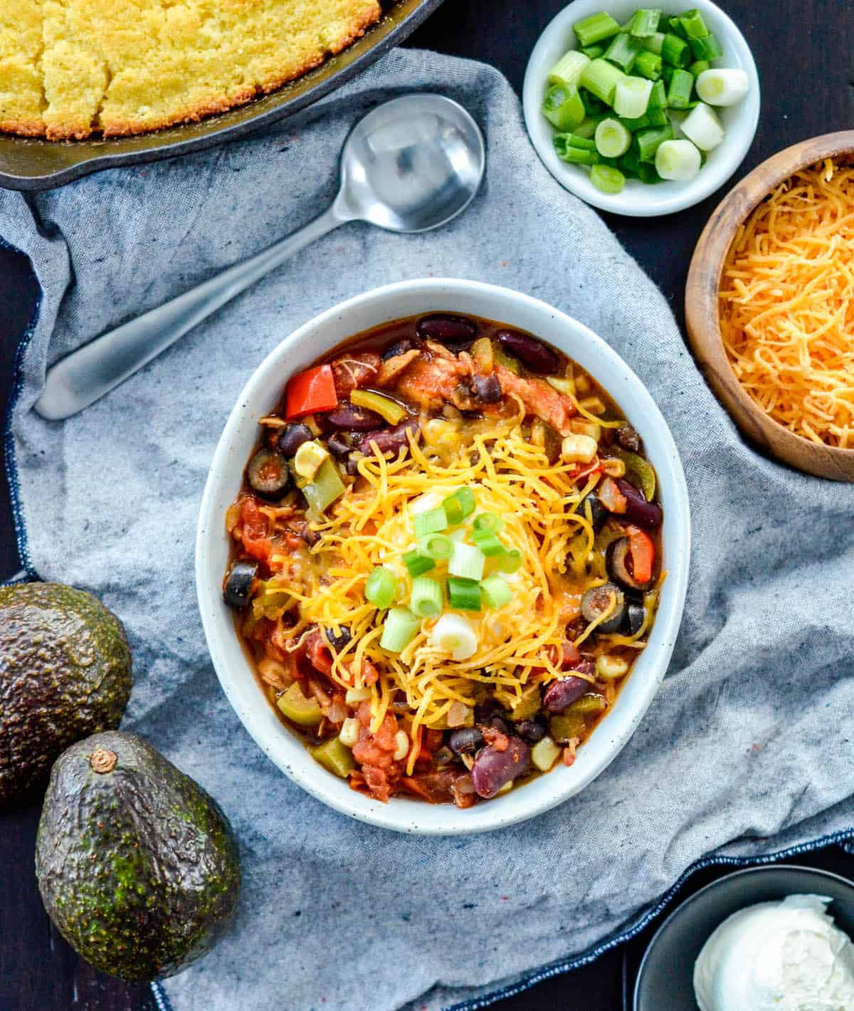 overhead view of The BEST Healthy Crockpot Chicken Chili with sour cream, cheese and green onions