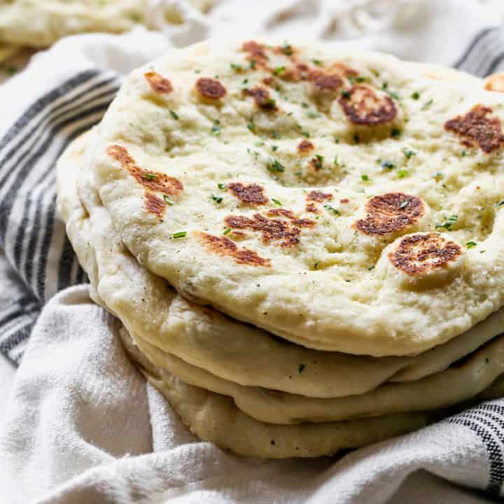 front view of a stack of four pieces of  homemade naan bread