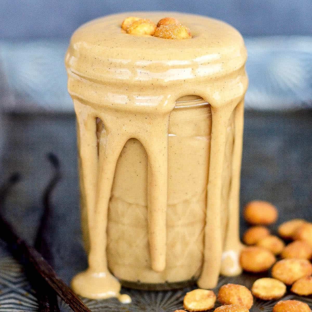 Front view of a jar of Honey Roasted Peanut Butter with some peanut butter dripping down the sides.