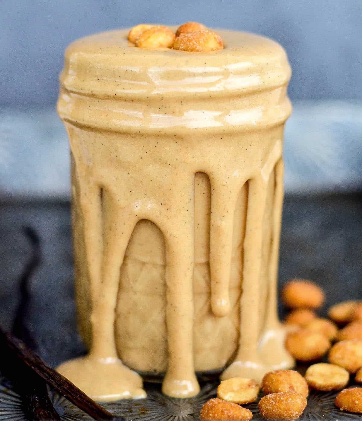 Front view of a jar with peanut butter dripping down the sides.
