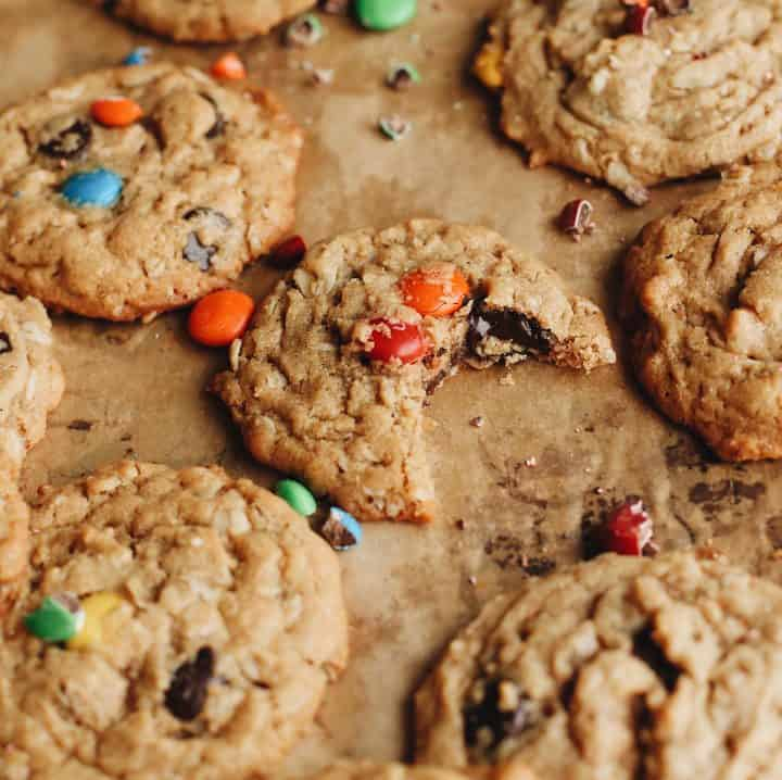 front view of a Monster Cookie with a bite taken out of it surrounded by 5 other cookies